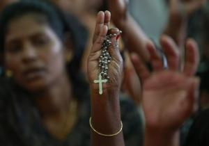 A protester holds a cross during a protest rally by hundreds of Christians against recent attacks on churches nationwide, in Mumbai