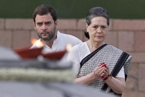 Chief of India's ruling Congress party Sonia Gandhi pays tribute at her husband Rajiv Gandhi's memorial as her son and a lawmaker Rahul Gandhi watches on the 21st anniversary of the former Prime Minister's death in New Delhi